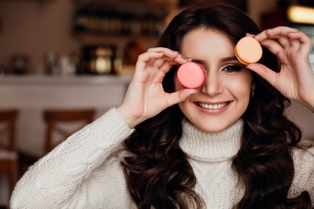 guilty pleasures: Young woman holding a bunch of colorful macaroons around her face and with on ein her mouse on blurred background, close-up plan