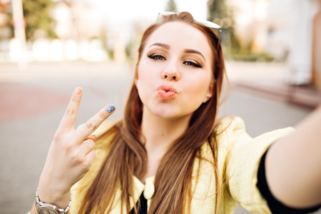 sexy pictures: Young sexy woman with bright make-up formic blond hair makes selfie sending a kiss, hipster street portrait. Shows a peace sign, taking pictures of herself Stock Photo