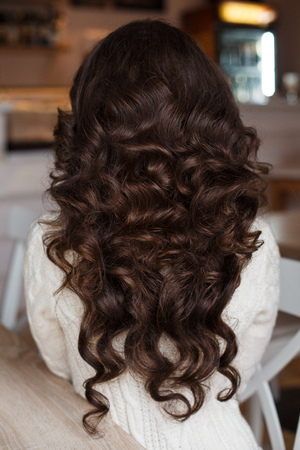 perming: The girl raises her long curly hair. The girl with well-groomed curly hair .