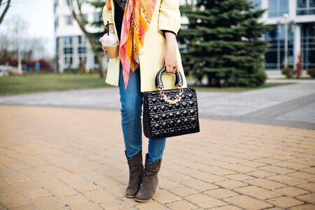 close-up portrait of a fashionable young lady posing in the city, accessories, spring shoes,perfect feet, the spring collection of boots,stylish gray ankle boots, fashionable yellow coat,black bag, coffee. Banco de Imagens
