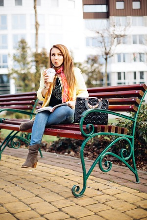 businees: Lifestyle young stylish woman sitting bench, listening to your favorite music, drinking coffee and reading a magazine. Dressed in a fashionable yellow coat, bright colorful scarf, denim dress, boots.