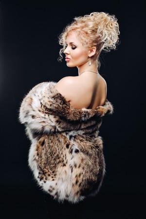 manteau de fourrure: Bijoux et dame de la mode. Belle femme portant dans le luxe Fur Coat sur. Portrait d'une femme en studio sur un fond noir en fourrure, maquillage de luxe, buste de luxe. Annoncez un manteau de fourrure de lynx. Banque d'images