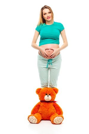 Pregnant young woman on white background making a heart on its stomach, a soft toy bear near her legs. Smiles,happy. The concept of motherhood