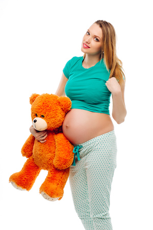 Pregnant in bright pajamas holding a stuffed toy in his hands, smiles, touches her hair. White background, isolated