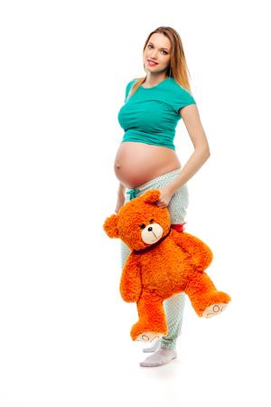 Mom in pregnancy holding a teddy bear.