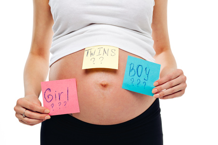 mellizos ni�o y ni�a: pregnant belly boy girl twins pictures on stickers, woman expecting baby, family parenting concept. young pregnant woman with sticker and question on it boy or girl or twins concept. expectant mother.