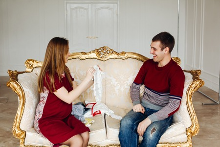 baby stuff: Young pregnant woman with her husband on a gold sofa in a bright room with baby stuff. The pair, dressed in maroon and blue.