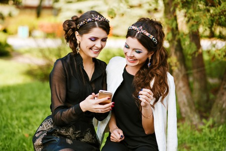 going crazy: Friend look at the phone and discuss something. Laughing and smiling, going crazy, having fun. stylish woman at the party with a bright evening make-up, fashionable jewelry. Bright colors, warm colors