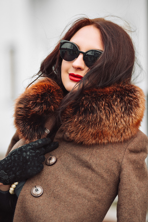 Beautiful Woman in Luxury Fur Coat. Stylish brunette woman in brown coat. young sexy sensual seductive woman with perfect fluffy curled hairs,amazing smile with brilliant white teet, vintage sunglasses