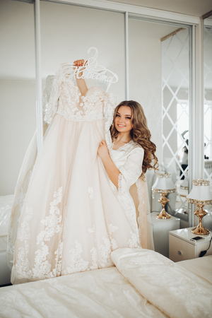 house robe: the bride holds the wedding dress, beautiful interior, long curly hair women