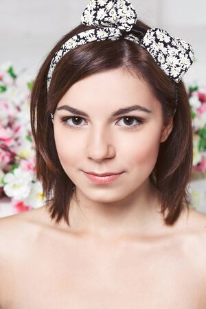 brown eyes: Beautiful young woman face closeup - perfect skin. Flowers background. Brown eyes