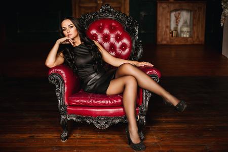 mooie jonge brunette vrouw met lang haar in zwarte jurk zittend in een stoel