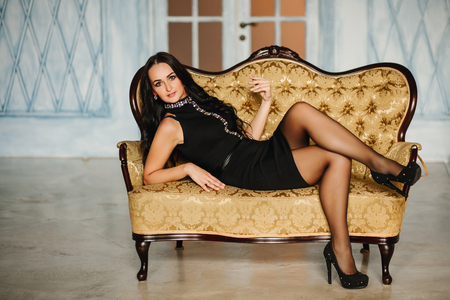 chesterfield: Elegant woman in black dress sitting on chesterfield armchair in classic vintage interior. Glamour Stock Photo