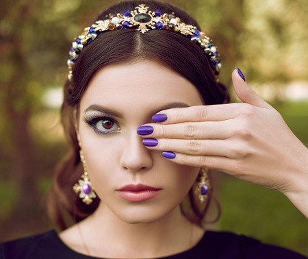 one eye: Close-up portrait of beautiful fashion woman with bright purple manicure, stylish makeup. The girl is holding a hand near the face, covering one eye. Manicure, design, fashion, make-up, brightly. The background is blurred Stock Photo