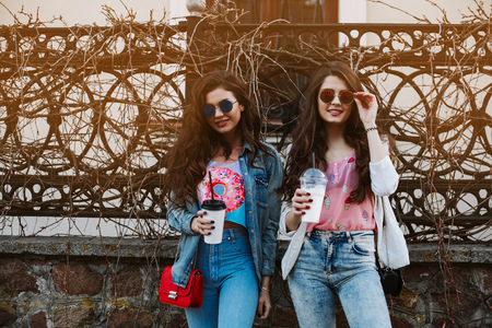 going crazy: Summer lifestyle portrait of two hipster stylish women with fit sexy body, wearing denim outfit and vintage sunglasses. Girls friends going crazy, having fun, dancing, laughing and screaming Stock Photo
