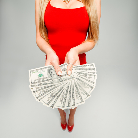 exaggerate: The girl holds in hands a lot of money. The woman in the red dress and red shoes with a fan of banknotes in his hands, his chest Stock Photo