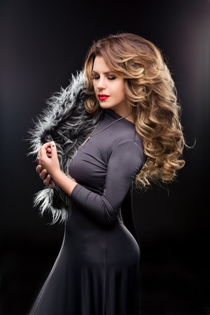 coloring lips: Fashion Studio portrait of beautiful woman in a gray dress with curvy figures. Slender girl with long hair. Hairstyle wavy hair streaked, makeup, red lips, fur. Black background