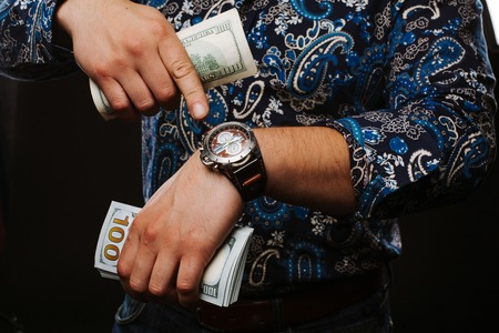 million dollars: Time is money. The concept of time and money. A man holding a lot of money and shows up on time Stock Photo