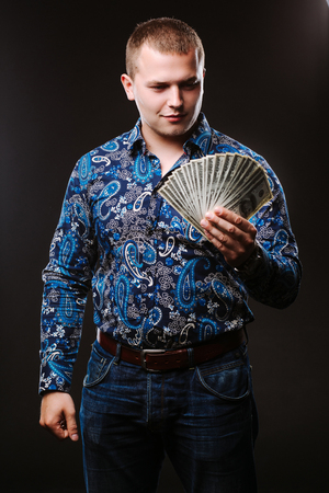 venal: Portrait of a man in a shirt and jeans holds a lot of hundred dollar bills. The guy is holding a salary, money