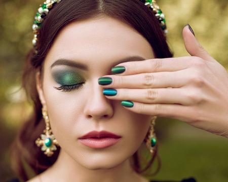piedras preciosas: Retrato de mujer hermosa, maquillaje y manicura en el mismo estilo, joyería con piedras preciosas. El maquillaje y la manicura verde, esmeralda Foto de archivo