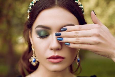 piedras preciosas: Retrato de mujer hermosa, maquillaje y manicura en el mismo estilo, joyería con piedras preciosas. Maquillaje verde, esmeralda y la manicura es de color azul.