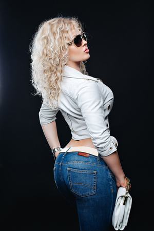 the caucasian beauty: Portrait of the lifestyle of fashionable young woman with curly blond hair, sunglasses, white leather jacket, blue jeans. Black background, Studio.