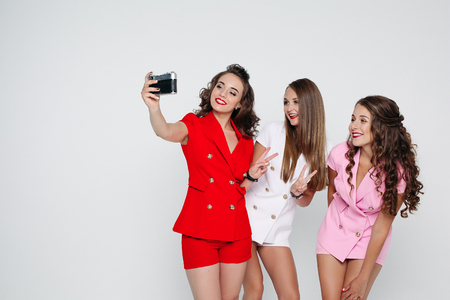 Fashionable girls in bright colorful suits taking selfie via fil