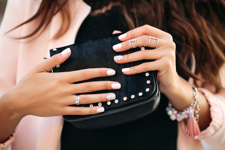 Female hands with beautiful nail polish and rings holding small black bag.