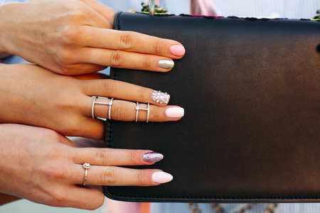 Girls showing her stylish manicure, holding thair fingers on black handbag.