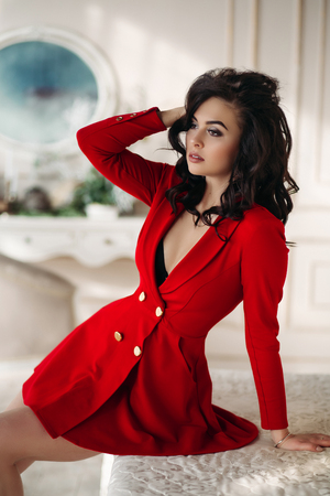 Seductive woman in red dress sitting on bed and touching hair. Stock fotó