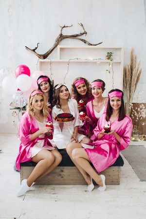 Bridesmaids with cupcakes and bride-to-be with cake.