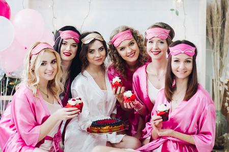 Chicas guapas con túnicas rosas y máscaras para dormir con postres en las despedidas de soltera.