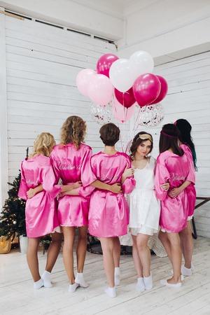 Longitud total de la novia en túnica blanca con damas de honor de pie bac
