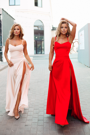 Gorgeous and attractive girls in long evening dresses posing.