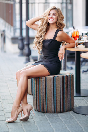 Attractive girl wearing black dress drinking cocktail and smiling.