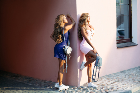 Attractive girls wearing little dresses and holding chic blue backpacks.