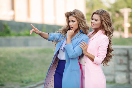 Two gorgeous business women standing and looking somewhere. Stock Photo