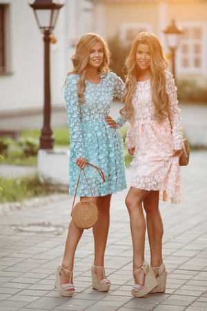 Pretty girls in rose and blue flowery dresses posing and smiling. Stock Photo