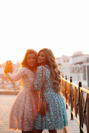 Beautiful ladies making photo at smart phone together.