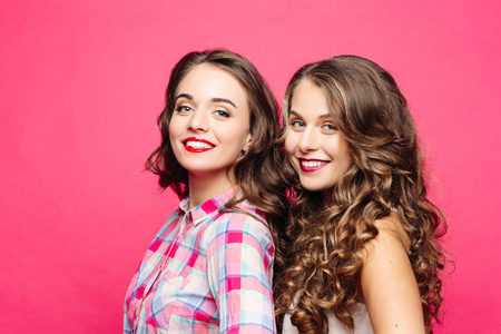 Studio view of beautiful girls with magnificent wavy hair and red lips, in a hipster style with a happy, cute, decomposing smile Isolate on a pink background. Stock Photo