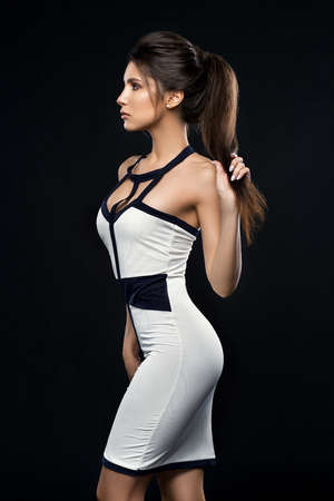 Sexy and stylish brunette woman in dress posing at studio.