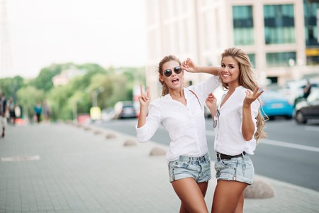 Beautiful women twins showing peace and emotionally posing. Stock Photo