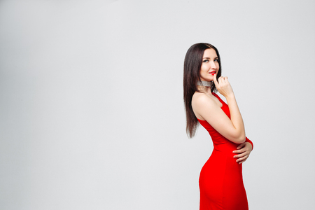 Seductive brunette in bright red dress and chocker with hand at Stock fotó