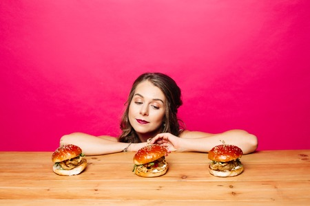 Sad girl looking at yummy fresh burgers with chicken on wooden table
