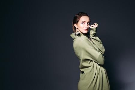 Elegant pregnant woman posing at dark studio.