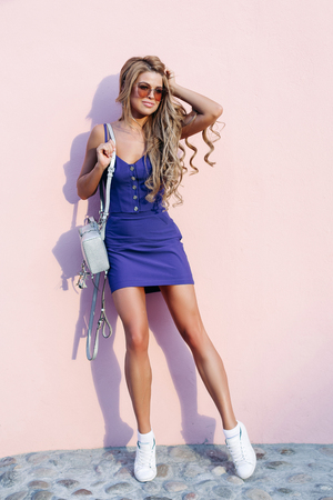 Seductive model with chic long legs posing near rose wall.