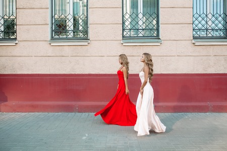 Confident and fashionable girls rising up her elegant evening dresses.