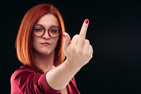 Confident and angry red haired girl showing finger, gesturing fuck off.