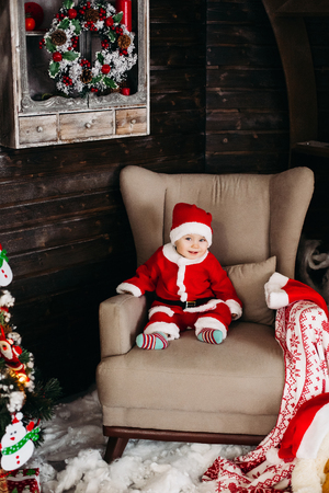 Little Santa boy in red suite sitting in big arm chair near Christmas tree. 스톡 콘텐츠