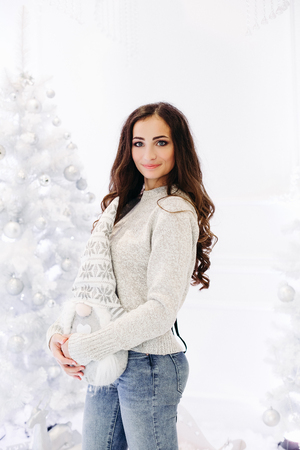 Gorgeous brunette woman posing in decorated studio against Christmas tree.